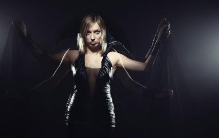 necromancer: Woman in Halloween witch costume moving hands. Long exposure studio shot