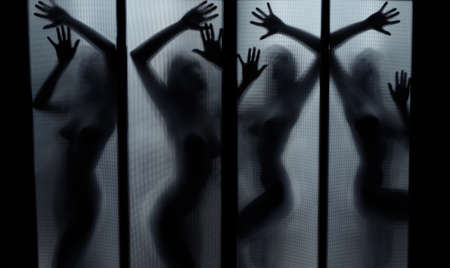Silhouette of the naked lady dancing behind the glass