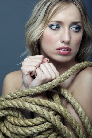 Suffering woman with hands tied by terrible rope photo