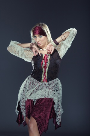 national costume: Lady in traditional costume performing national dance on a dark background