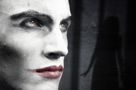 Face of vampire on a dark grungy background with woman shadow photo