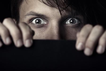 Afraid human hiding behind the dark board