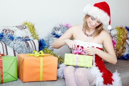 jot: Smiling lady in the red furry Santa Claus costume and hat holding Christmas gifts Stock Photo