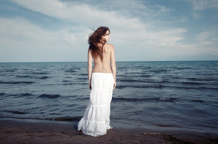 Single topless lady standing at the waving ocean. Rear view. Artistic colors added Stock Photo - 11032604