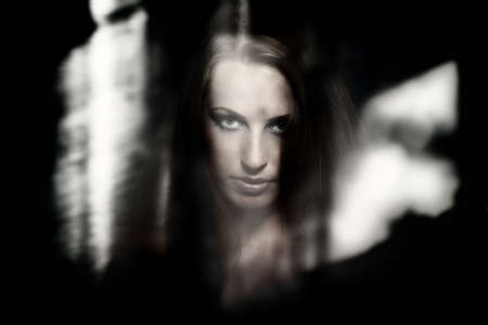 ghost face: Female witch behind the dark glass with reflections Stock Photo