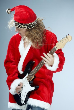 songster: Man in the red and furry Santa Claus costume playing rock guitar