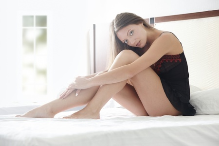 bedstead: Young lady at home sits on the bed at early morning Stock Photo