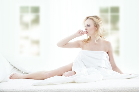 Blond lady sits in the bedroom at early morning photo