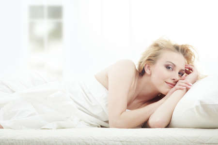 Blond lady laying in bedroom at early morning photo