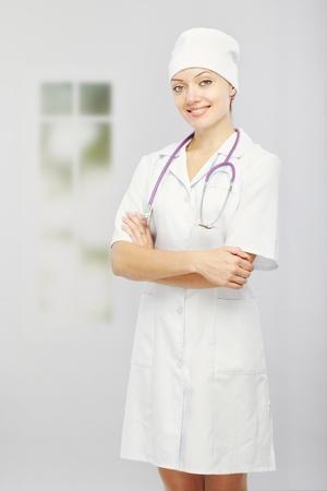 nurse cap: Mujer sonriente en uniforme médico en el hospital junto a la ventana Foto de archivo