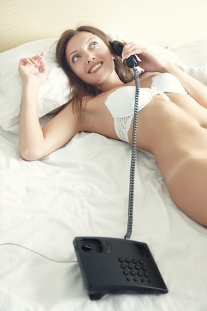 Naked lady laying on the bed and talking via telephone at the early morning. Natural light and colors Stock Photo - 11574323