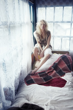 Single blond lady sits on the bed at home photo
