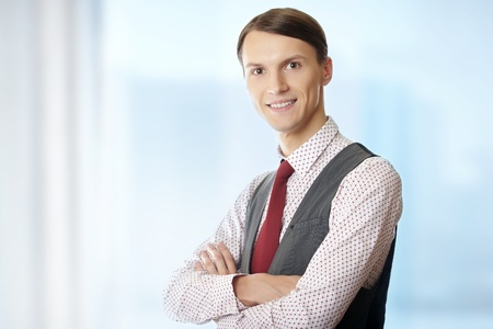 Smiling businessman with arms crossed in his office photo