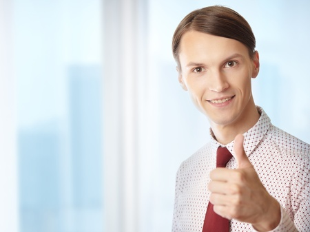 Successful businessman making thumbs up gesture in his office photo