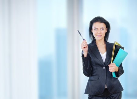 business attire teacher: Successful businesswoman stands in office with documents and pen
