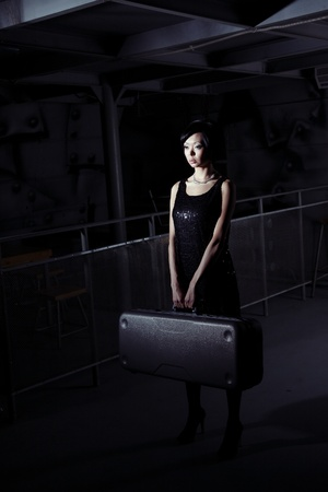 Small brunette lady holding big suitcase in the dark airport terminal photo