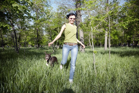 Smiling happy lady runs with her dog in outdoors park photo