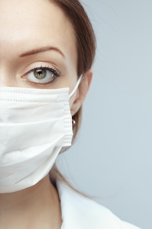 Female doctor in protective mask on a blue background photo