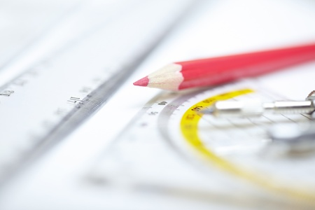 Red pencil with compasses and rulers on a paper. Extremely close-up photo Stock Photo