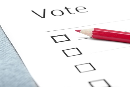 Voting bulletin with red pencil on a table photo