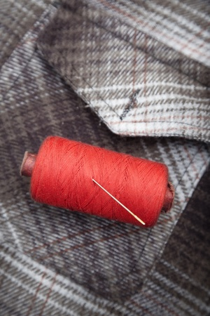 flannel: Red sewing spool with needle on a flannel fiber. Close-up photo