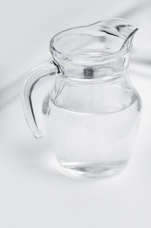 jug: Transparent glass can with water on a table with shadows