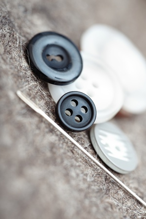 Buttons and sewing needle. Extremely close-up photo with shallow depth of field photo
