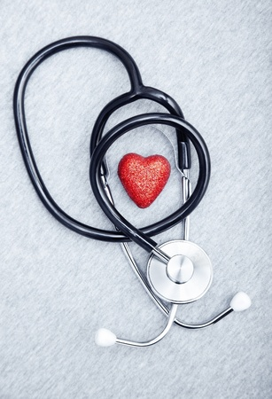 cardiosurgery: Medical stethoscope and heart on a textured background