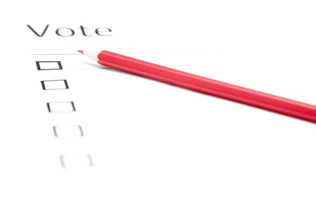 Voting bulletin with red pencil. Close-up photo with shallow depth of field photo