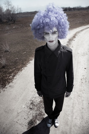 Sad clown outdoors standing on a country road photo