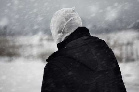 succubus: Rear view on the human with bandaged head under the nuclear snowstorm Stock Photo
