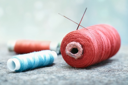 stitching: Sewing spools on a woolen fiber. Close-up photo