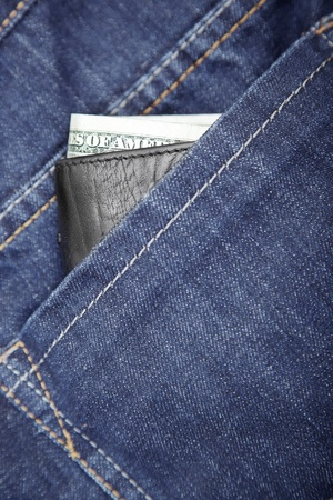 notecase: Wallet with dollars in the jeans pocket. Close-up photo