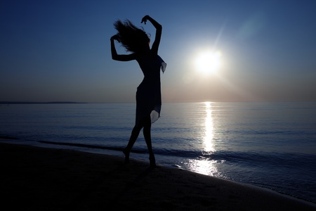 Silhouette of the woman with long hairs dancing at the beach during sunset. Artistic colors added photo