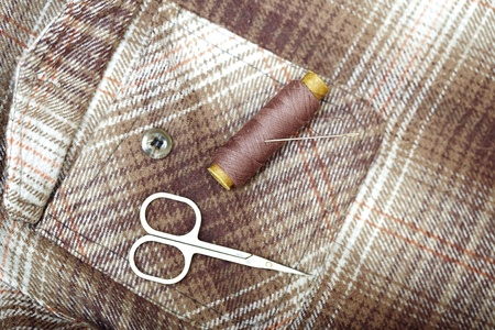 Sewing tools on a brown textile. Horizontal picture photo