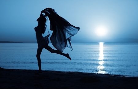 Silhouette of elegant lady dancing at the beach under the moonlight photo