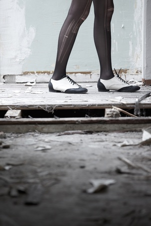 brogues: Human legs in stylish shoes standing in the ruined dirty room