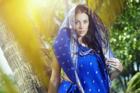 Beautiful lady in blue sari posing in the wild jungle photo