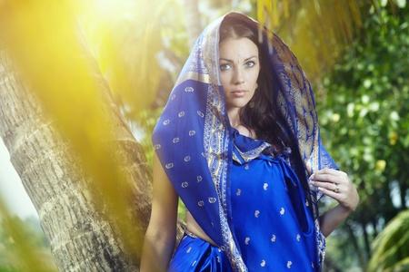 Beautiful lady in blue sari posing in the wild jungle photo