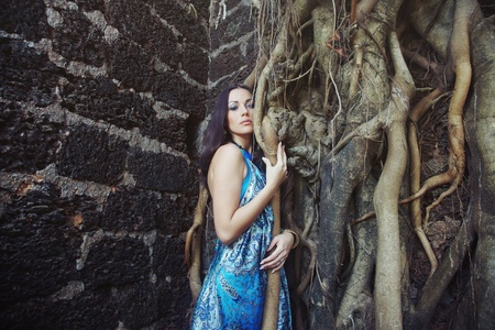 Sad pensive woman at the old banyan near the ancient stony wall photo
