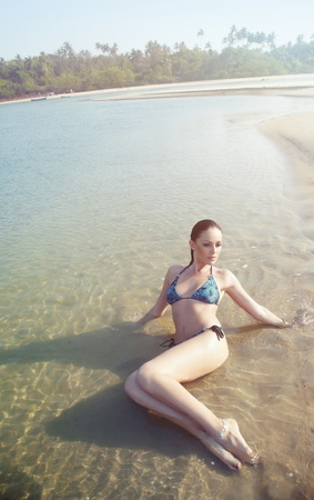Beautiful lady lays at the summer beach photo