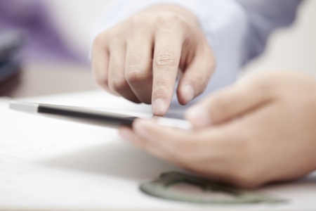 Hands of businessman using tablet PC at office Stock Photo - 14276851