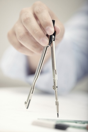 protractor: Hand of engineer working with compasses