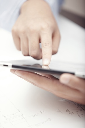 Hands of businessman using tablet PC at office photo
