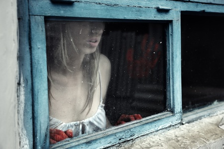 Woman with bloody hand behind the window photo