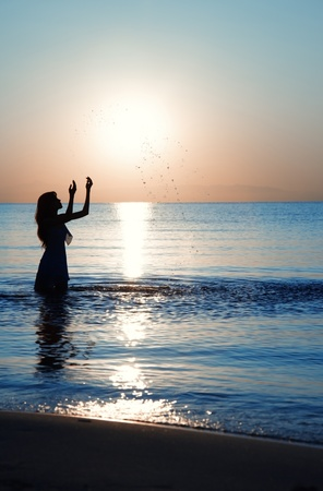 Silhouette of the lady playing with water during sunset photo