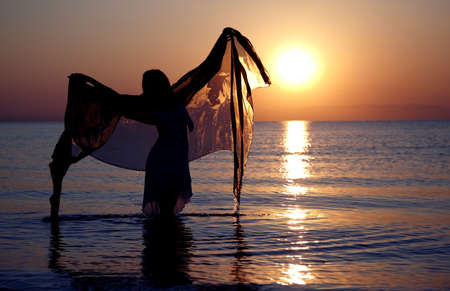 Silhouette of the woman dancing with fiber at sunset beach photo