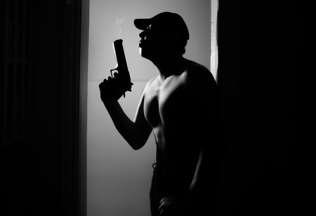 Silhouette of the muscular man with fuming gun in the dark interior.   Stock Photo - 14620524