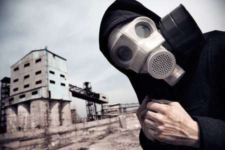 greenhouse gas: Human in gas mask outdoors and industrial factory on a background