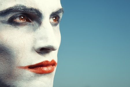 Sad clown with makeup on a blue background photo
